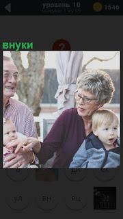 На скамейке бабушка с дедушкой, а на коленях внуки сидят