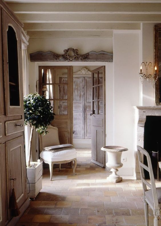 Weathered stone floor, antique armoire, and limestone fireplace in this elegant #Frenchfarmhouse on Hello Lovely Studio