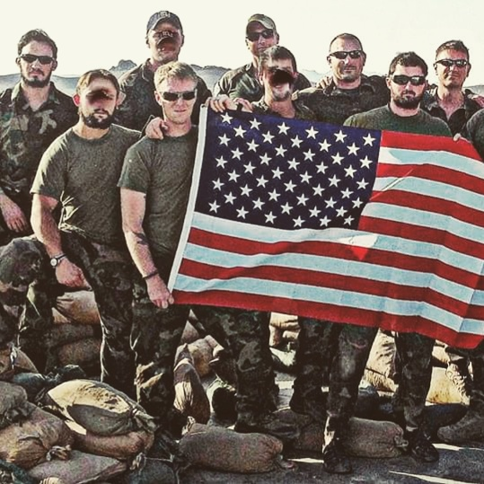 group of soldiers standing with an American flag