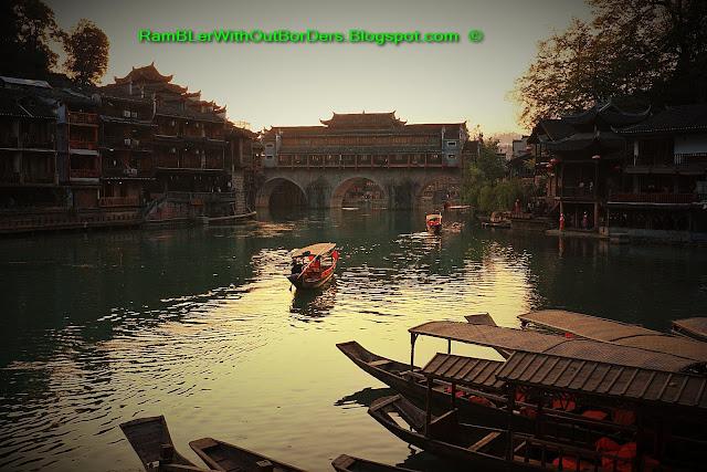 Boats moving under Rainbow Bridge, Riverside, Phoenix Fenghuang County, Hunan, China