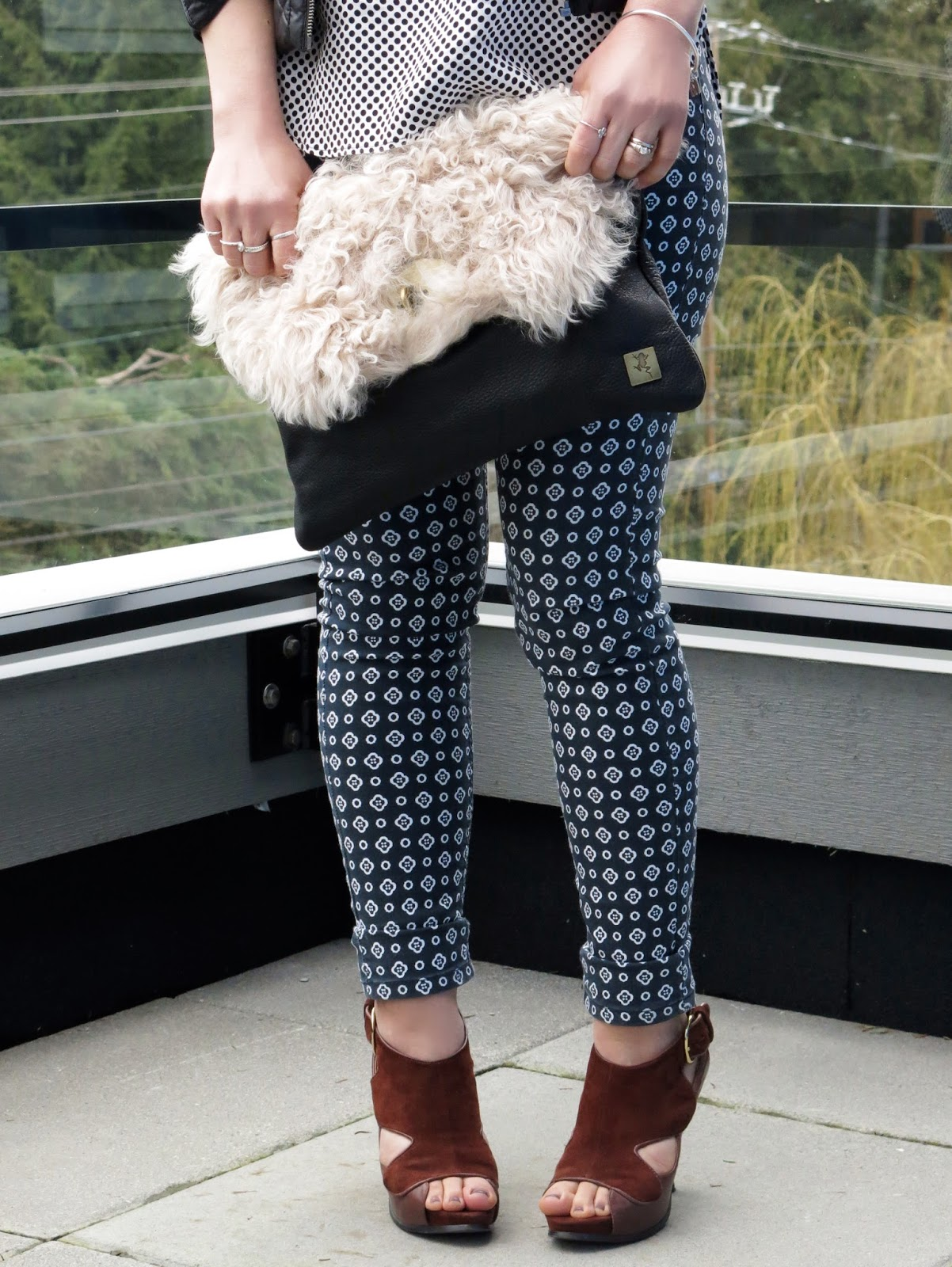 printed pants, polka-dotted blouse, and sherpa bag