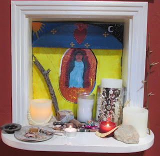 Simple altar painted yellow background with sun in one corner, stars in the other. A woman deity is centered in a blue dress and surrounded by red and gold. A circle of black, blue yellow and white outline the center circle. On the altar are lights, candles, desert twigs and seed pods. Also there are small sacred objects including a turtle, copal and sage.