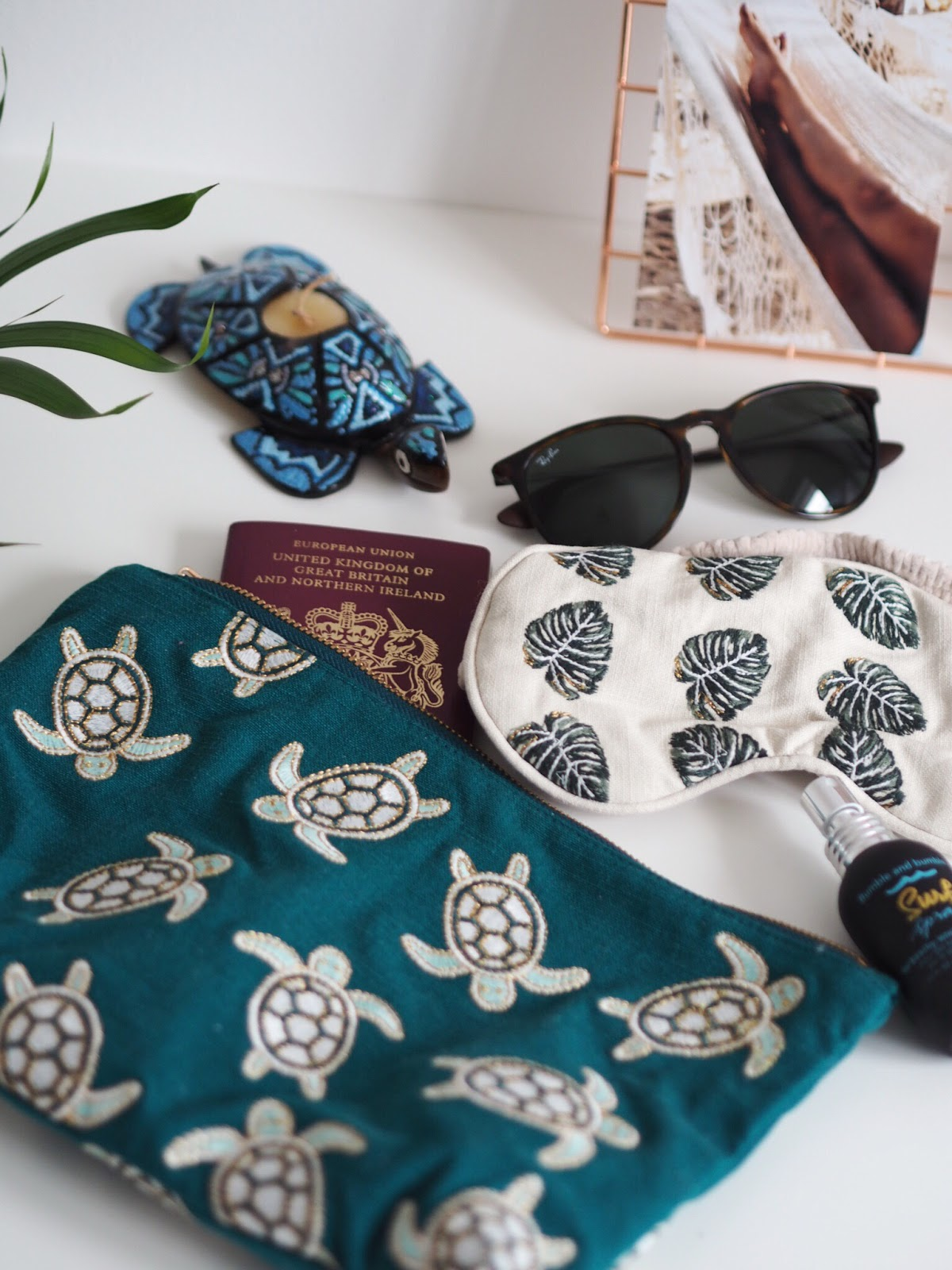Elizabeth Scarlett Turtle Pouch, Elizabeth Scarlett Jungle Travel Eye Mask, Ray Ban Sunglasses, Passport, Bumble Bumble Salt Spray Holiday Essentials Flat Lay