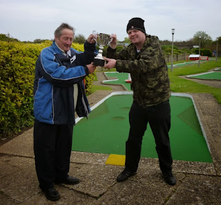 Brad receives the Skegness Minigolf Championship trophy from reigning Holiday on the Buses Butler Cup Champion Eric Huckle