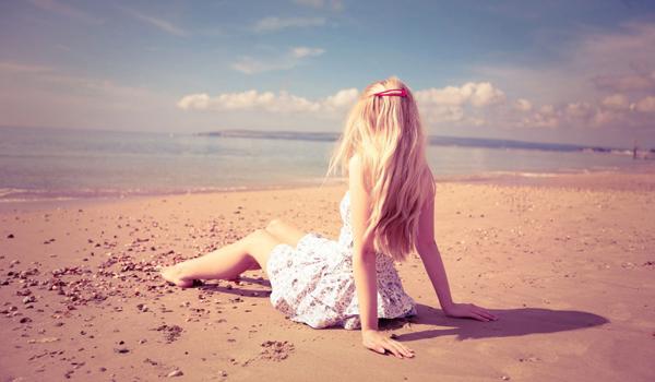 Mulher nova sentada na areia da praia olhando o mar