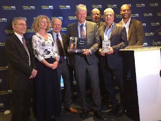 William Finnegan  (centre) shows off the 2016 William Hill  Sports Book of the Year Award, flanked by (left-to-right)  judges Graham Sharpe, Alyson Rudd, Hugh McIlvanney, Mark Lawson, John Inverdale and Clarke Carlisle.
