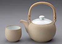 Bambu saplı krem rengi seramik çaydanlık ve yanındaki kupası