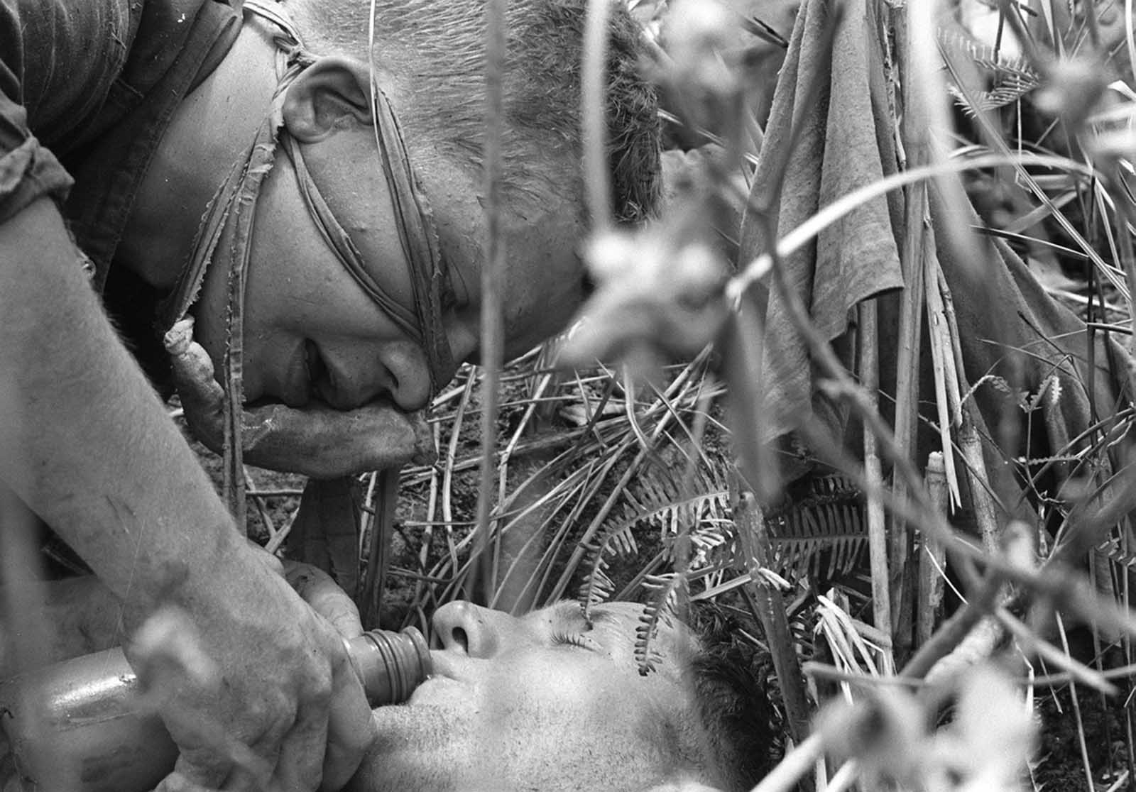 A Marine, top, wounded slightly when his face was creased by an enemy bullet, pours water into the mouth of a fellow Marine suffering from heat during Operation Hastings along the demilitarized zone between North and South Vietnam on July 21, 1966.
