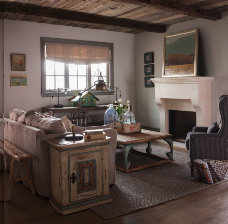 Nordic French living room with rustic wood ceiling and limestone fireplace. Come see this Rustic Elegant French Gustavian Cottage by Decor de Provence in Utah! #frenchcountry #frenchfarmhouse #interiordesigninspiration #rusticdecor #europeanfarmhouse #housetour