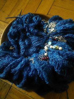 A knit lace scarf scrunched up on a circular needle and tucked into a yarn bowl. The scarf is knit in deep blue fingering yarn.  There are a large variety of stitch markers hooked into the work.
