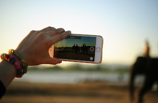 image of a person recording a video using their smartphone