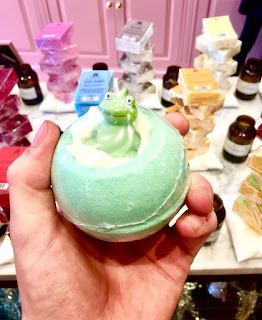 A bright green spherical bath bomb held in a pale pink hand with a green miniature rubber frog on the top on a bright background