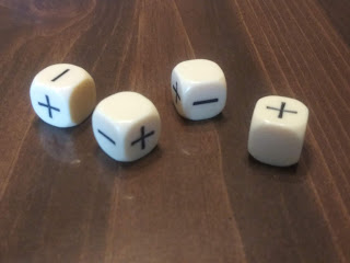 Four ivory-coloured plastic dice, each marked with pluses and minuses instead of numbers, on a glossy wooden surface.