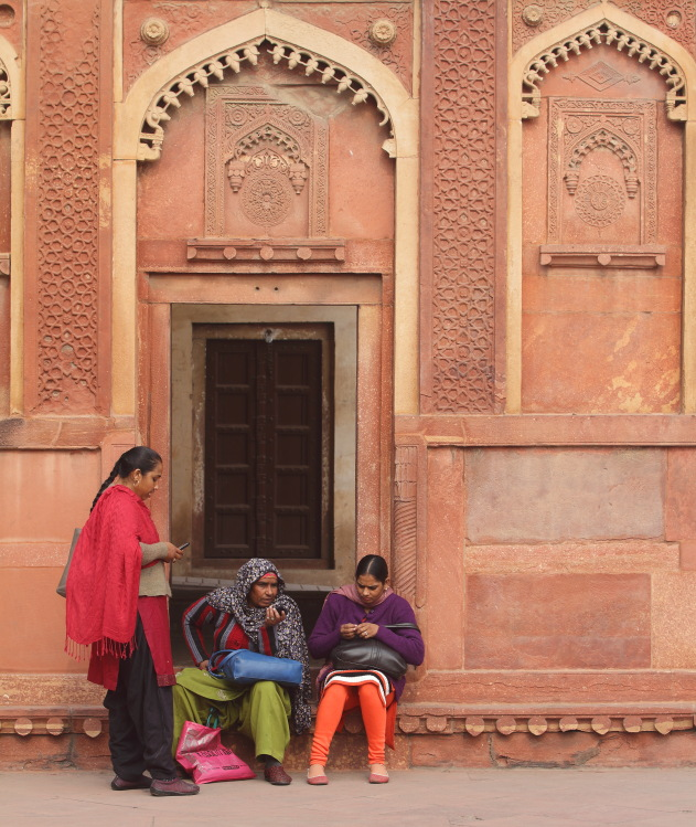 Local ladies gossip session in front of an ornate door, Red Fort, Agra, India