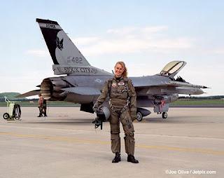 Dados técnicos: Um F-16 tem a maioria dos elementos encontrados em um jato de caça comum: duas asas que geram sustentação, estabilizadores traseiros verticais e horizontais, lemes que equilibram e direcionam o avião, além de motores de jato turbofan duplos na traseira os quais geram empuxo. O corpo do avião também é relativamente leve, apesar de ser extremamente resistente. Os apoios da asa (estruturas de suporte dentro das asas) são feitos de titânio, que são mais leves e mais resistentes que o aço; a maior parte da fuselagem é feita de alumínio. O peso normal do F-16(vazio) é de 8,495 kg. Canopy - Cobertura transparente de Plexiglass sobre o cockpit de aviões de caça. GPU (Ground Power Uni) - Gerador para suprimento de eletricidade para aeronaves em solo Descrição da foto: Foto em dia claro em parte de uma pista de pouso na base aérea do Alaska. Em foco, a Maj. Bobbi Doorenbos, em pose para a foto, em pé, de frente em um largo sorriso, segura com a mão direita o capacete apoiado na coxa. Atrás, o imponente caça F-16 estacionado com inclinação à direita, canopy levantado, corpo médio prateado, asa curta com equipamento de bombardeio na extremidade, estabilizador vertical alto em preto e branco com pintura de um morcego com as asas abertas, abaixo, o prefixo: AF85 482, em seguida: SIOUX CITY e no topo lê-se:IOWA, a cauda é composta pelo motor de pós-combustão. A major Doorenbos, é uma mulher jovem, loira, com cabelos presos, franja penteada à direita, rosto oval, sobrancelhas retas, olhos amendoados, nariz afilado, lábios médios e dentes alvos; ela usa um macacão militar verde amarronzado com zípers no peito e pernas, luvas, cinto de segurança do paraquedas nos ombros, extensões trespassadas na virilha e coturnos pretos. Ao fundo, à esquerda, dois mecânicos próximos a um GPU quadrangular branco, de tamanho médio com a mangueira preta enrolada, presa no equipamento e além do gramado bem aparado,uma arborização desponta, finalizando em uma colina.