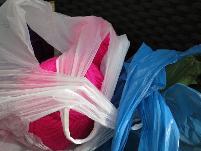 Pink knitting yarn in white plastic bag. Leeks in blue plastic bag.