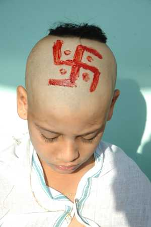 Hindu child with head shaven and red Swastika painted on it as part of his Upanayana ceremony