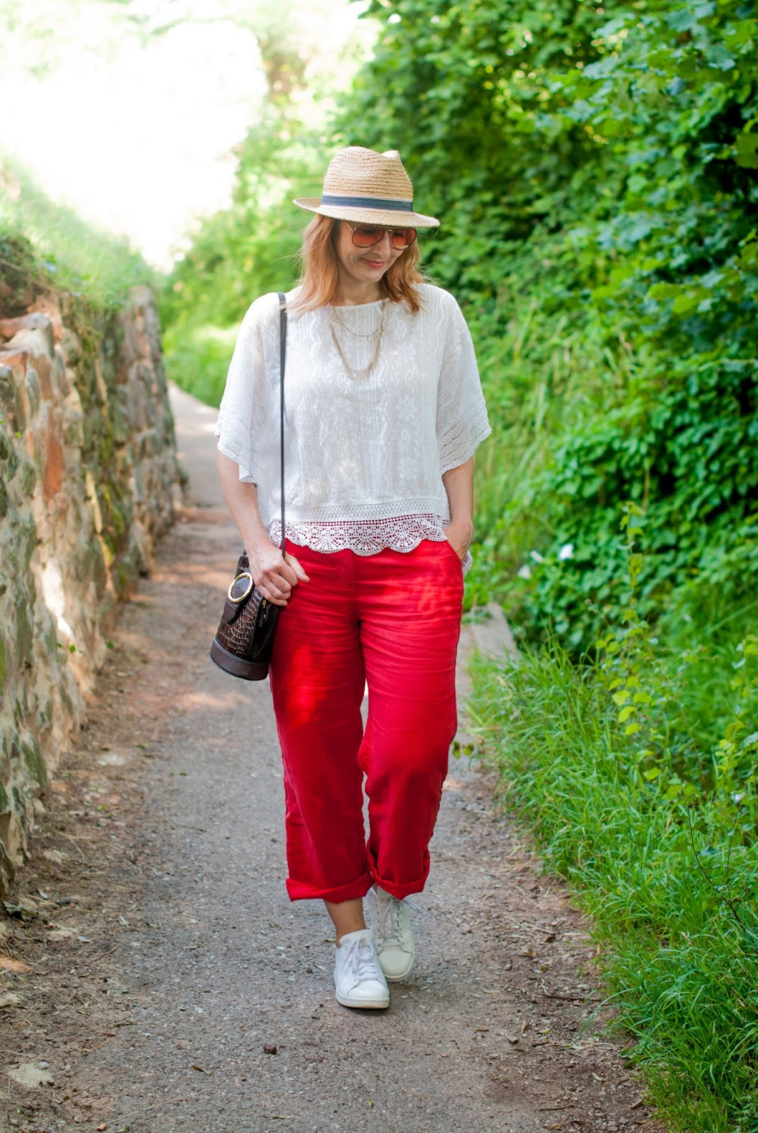 Red and white: A bold summer combination \ loose white lace top \ red wide leg linen pants \ straw hat \ white Adidas Stan Smiths \ orange tint aviator sunglasses | Not Dressed As Lamb, over 40 style