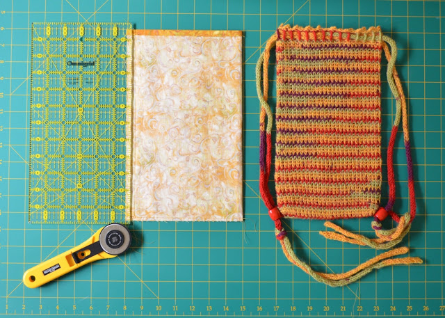 Almost the same as the previous photograph, the lining is laid out on the grid next to the bag.  A quilter's rule is on the left hand edge of the lining to trim the seam allowance. The rotary cutter is pointing to that edge.