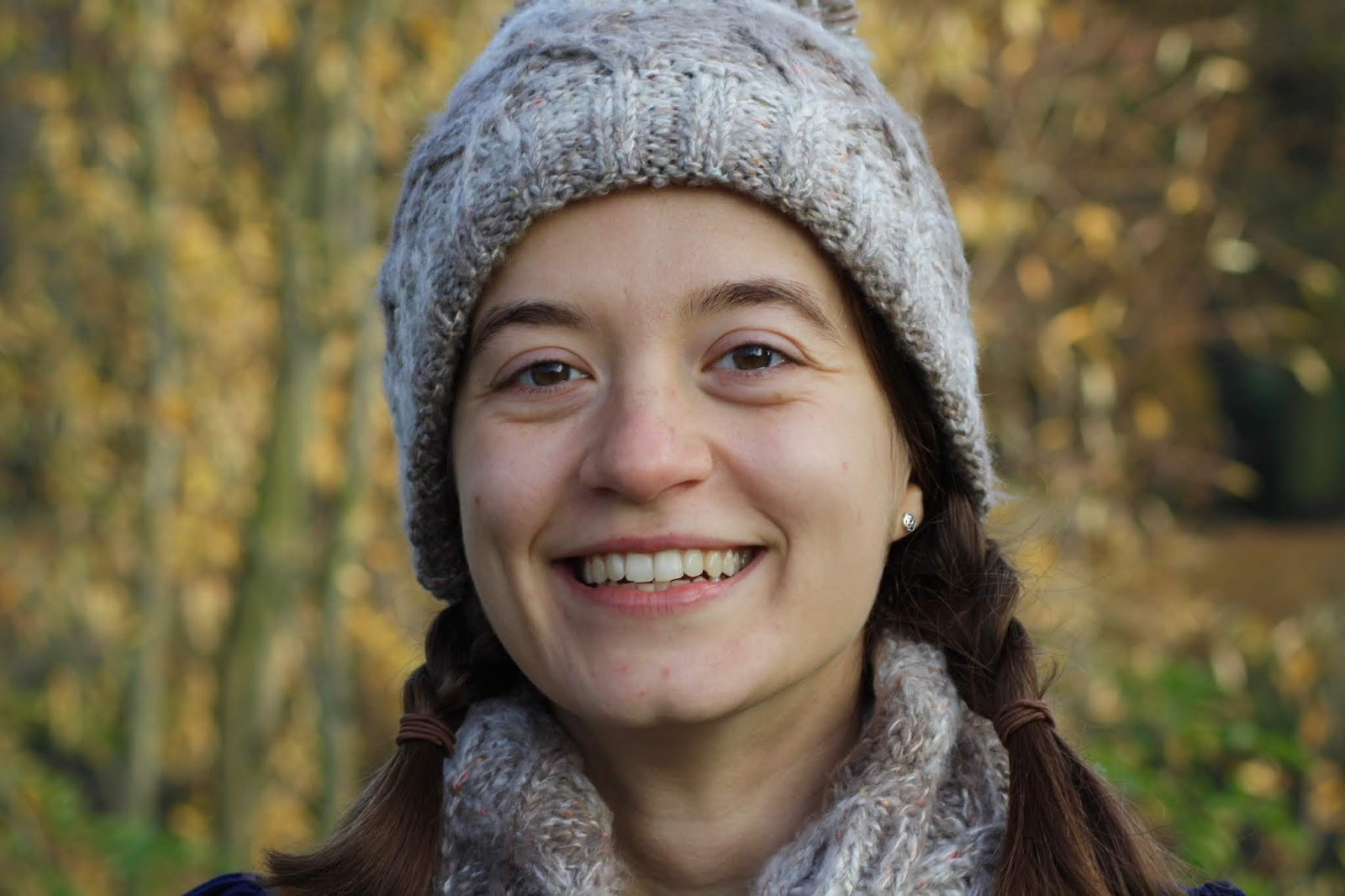 close up of smiling abbey, wearing brown knitted beanie and neck warmer