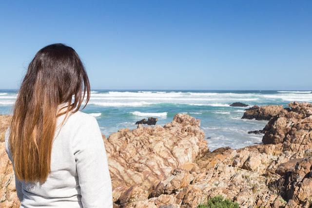 Lena mirando al mar en busca de ballenas en Hermanus, Sudáfrica