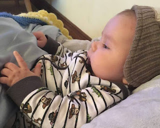 A side view of baby tucked in with the blanket folded back. He is touching the satin lining with his fingers and looking at them.  He is wearing a grey striped cap and a white top with dark thin stripes and dark cuffs. The satin lining is light blue.