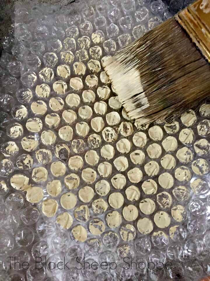 Applying paint to bubble wrap to create a honeycomb effect.