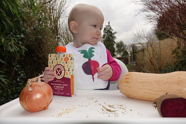 A baby sitting in a high chair in the garden holding a Babease pouch with a butternut squash, beetroot and onion on the highchair tray