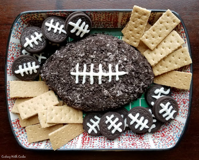 platter with football shaped cookies and cream cheese ball, graham crackers and chocolate cookies with frosting laces for dipping