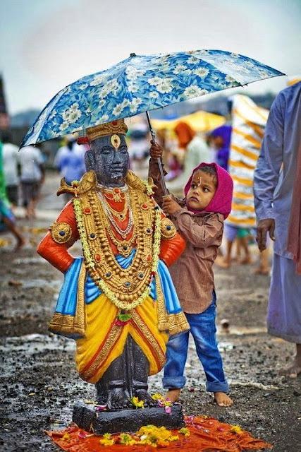 Bhakti is science boy holds umbrella over Vishnu idol