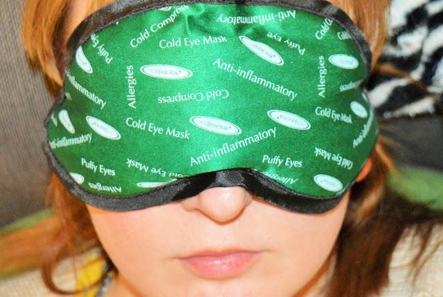 A lady (me!) wearing a green, white and black eye mask.