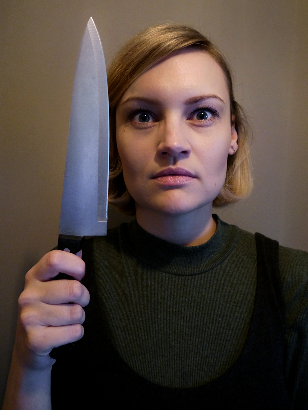 Kimberley from Wardrobe Conversations dressed as Annie Wilkes from Stephen King's Misery novel, holding a kitchen knife and looking menacing
