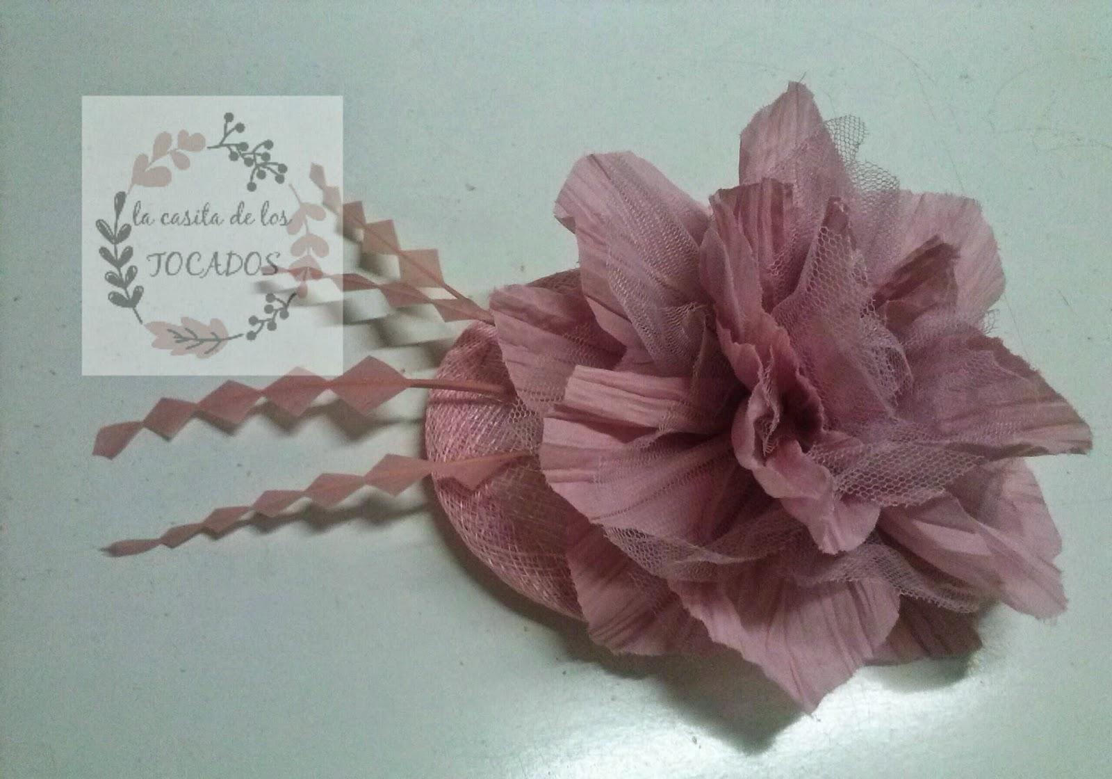 tocado con base de sinamay redonda, flor de organza y tul, y plumas de pato en rosa maquillaje