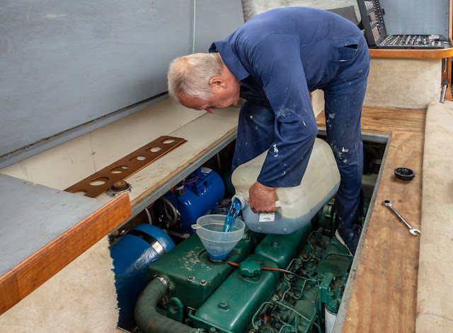 Photo of Phil pouring the new antifreeze/water mixture into the starboard engine