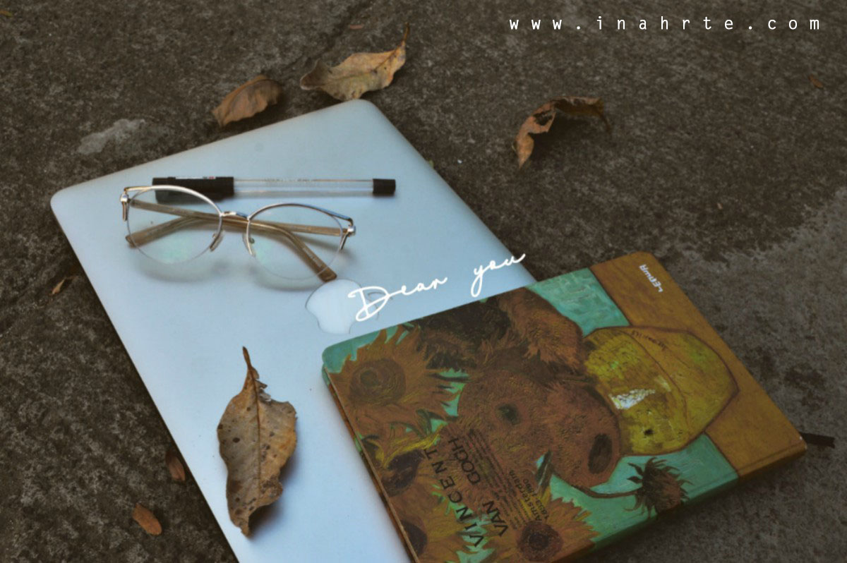 Flat lay laptop glasses pen notebook outside