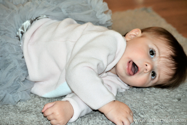Charlotte lying on the carpet in a grey tutu skirt