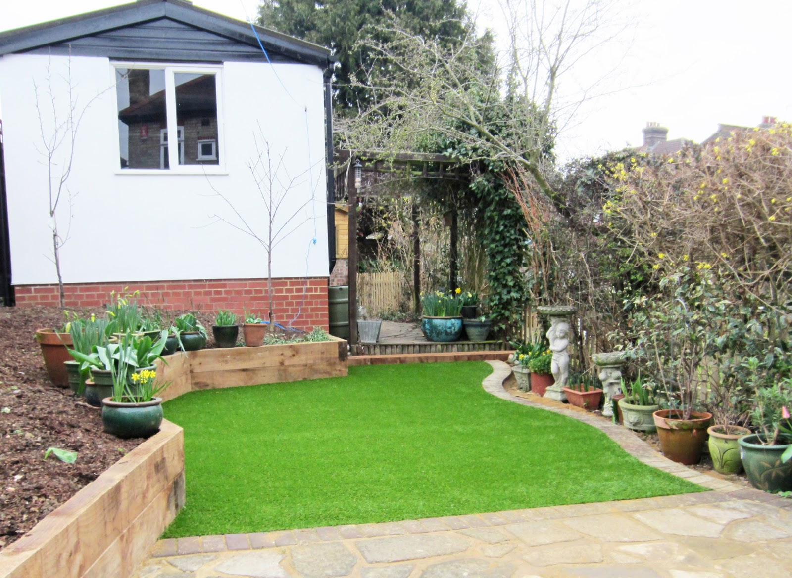 A London back garden after its makeover. Artificial grass has been laid in the north facing plot and wooden sleepers edge the border. Fruit trees have been planted and pots are full of spring bulbs.