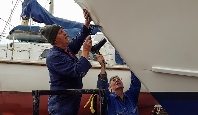 Photo of Photo of Phil and a friend applying the new trident logo on Ravensdale's bow