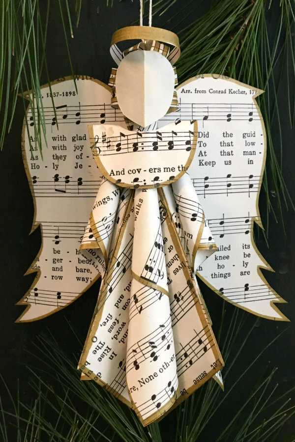 sheet music angel ornament with gold metallic inked edges hanging on tree