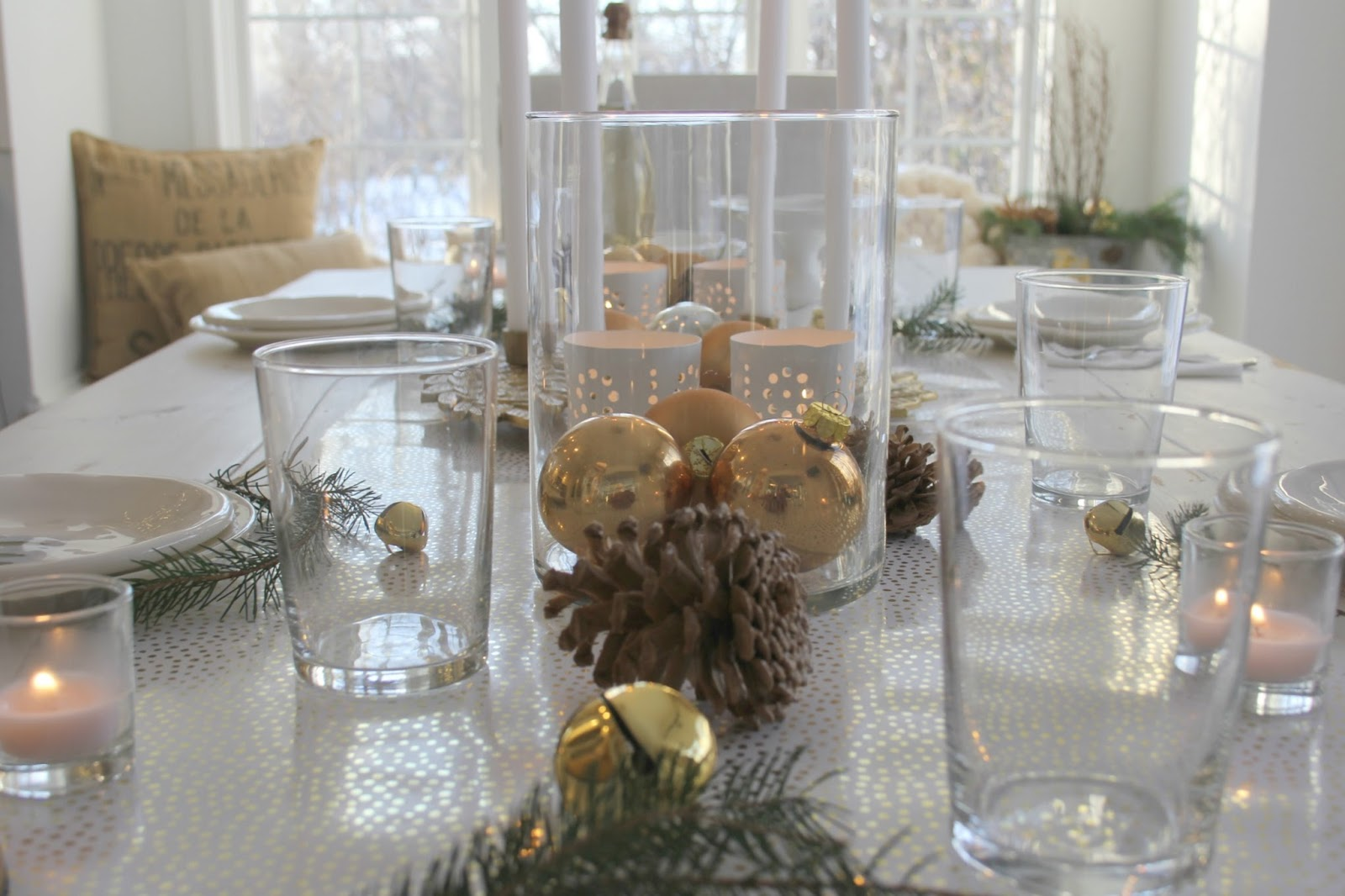 White gold and green Christmas decorated tablescape on white farmhouse table