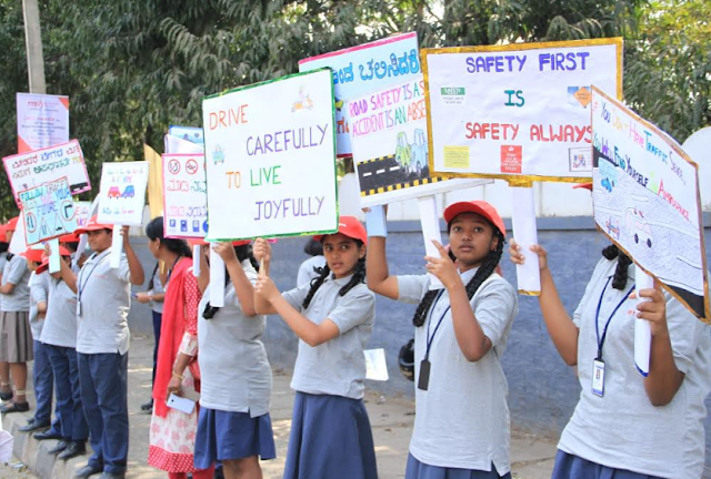Young safety ambassadors from Police Public School displaying road safety slogans at Madiwala during the inauguration of Toyota Safety Education Program