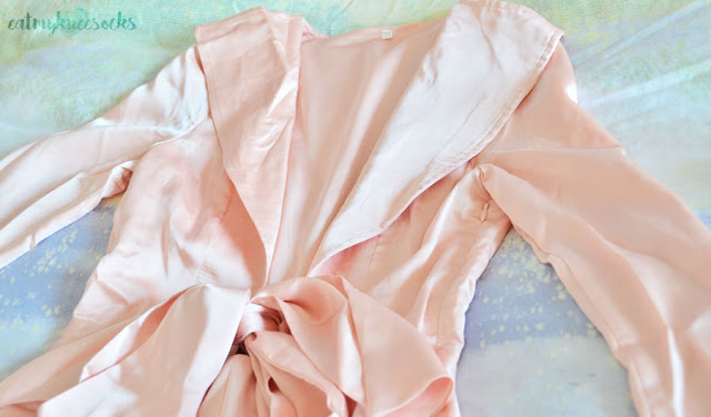 Light silky satin pastel pink long sleeve plunging tie-waist romper from SheIn, a dupe of the Nasty Gal version