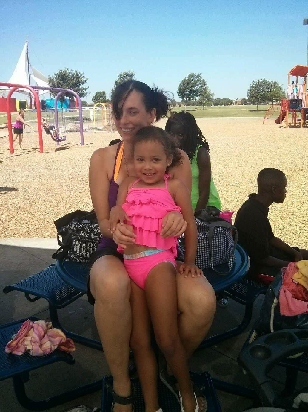 Image is a small medium skinned smiling girl with curly dark hair smiling standing in front of a lighter medium skinned female presenting person with dark hair in pigtails, also smiling. The little girl is wearing a hot pink swimsuit; the adult is wearing an orange swimsuit & purple tank top.