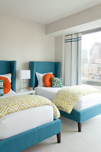 Clean and modern twin bedroom with white walls and floor, the turquoise upholstered beds have a wing back headboard, the orange accent pillows and a green and white down comforter folded across the bottom of the beds add a pop of color.