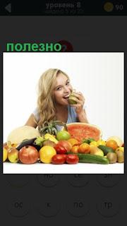 девушка за столом с фруктами и ест полезную грушу
