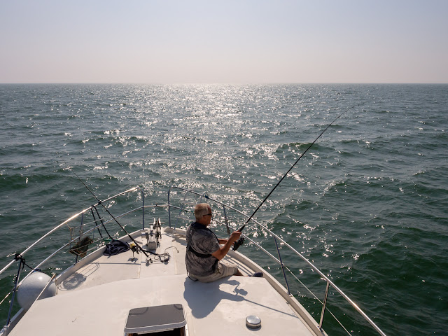 Photo of Phil fishing from Ravensdale's foredeck in the sunshine