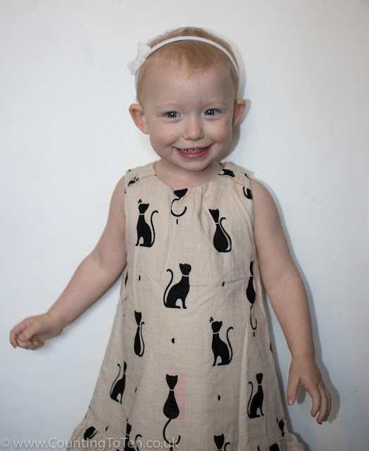 Little smiling and wearing the linen style cat print dress from the Fearne by Fearne Cotton mini club collection