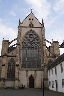 Man sieht hier die Westseite des Altenberger Doms von außen. In der Bildmitte befindet sich das große Westenster, darunter ein Eingqangsportal.