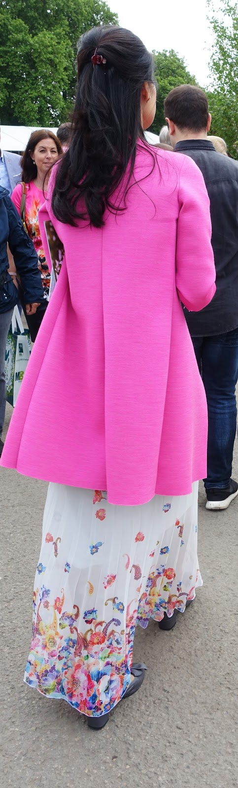 Rear view of a gorgeous fuchsia pink jacket and long skirt at the Chelsea Flower Show 2017