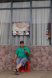 Man in chair in front of restaurant in Puriscal.